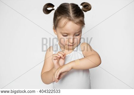 Adhesive Plaster Bandage On Wound Of Childs Arm, Medicine And First Aid Care. Injured Little Girl Su