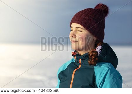 Beautiful Young Relaxed Woman Is Enjoying Sunny Weather In Warm Winter Clothes, Hat At A Cold Winter