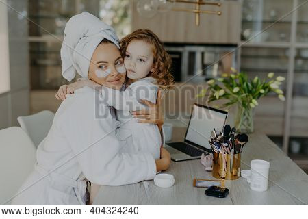 Attractive Woman Wears Hydrogel Patches Under Eyes Dressed In Bathrobe And Wrapped Towel Embraces He