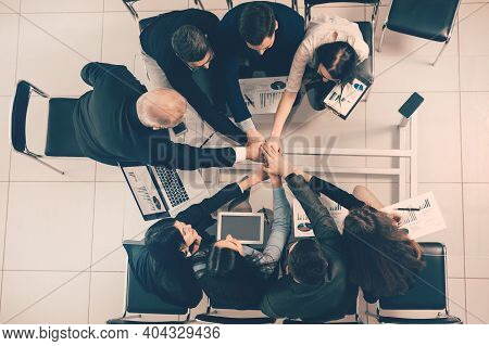 Top View. Happy Employees Joining Their Hands Over The Desktop.
