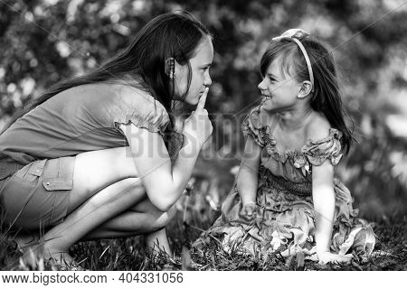 Girl with her finger over her mouth shows for mischievous child - Shh. secret. Black and white photo.
