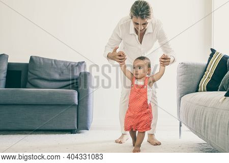 Front View Of Mom Holding Little Girl Hands And Helping To Walk. Cute Barefoot Baby Girl In Red Dung