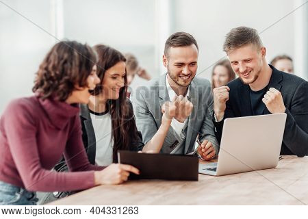 Admiring Group Of Employees Looking At Laptop Screen