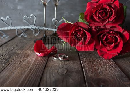 Red Roses Bouquet With Wedding Rings On Wooden Background. Atmospheric Declaration Of Love In Vintag