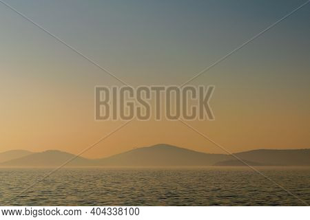 Hazy Sunset Seascape With Sea Horizon And Clear Sky, With Mountain Islands In The Far End, Princes I