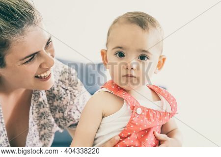 Happy Mother Holding Baby Girl, Smiling And Looking At Her. Serious Adorable Toddler In Red Dungaree