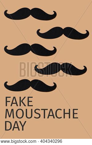 some moustaches, made with cutouts of a black cardboard, and the text fake moustache day on a brown background