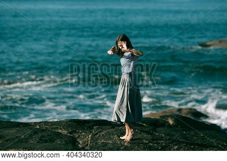 Young dancers woman is engaged in choreography on the rocky coast of Atlantic ocean. Portugal.