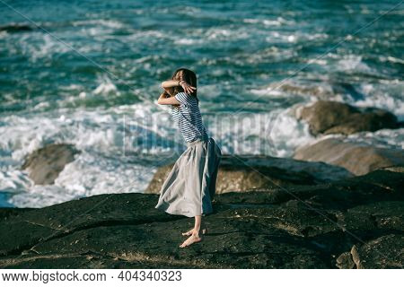 The young dancers woman is engaged in choreography on the rocky coast of Atlantic ocean. Portugal.