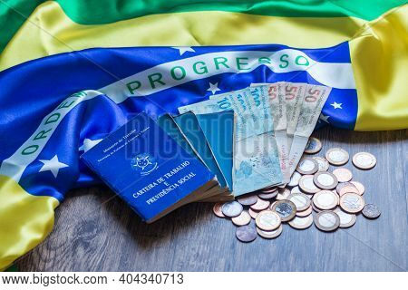 Brazilian Document And Social Security Document And Brazilian Currency On Brazilian Flag.