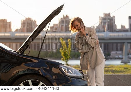 Helpless Woman Driver Calling For Help Assistance Looking At Broken Down Car With Opened Hood, Talki