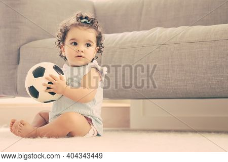 Pensive Sweet Black Haired Baby Girl In Pale Blue Clothes Sitting On Floor At Home, Looking Away, Pl