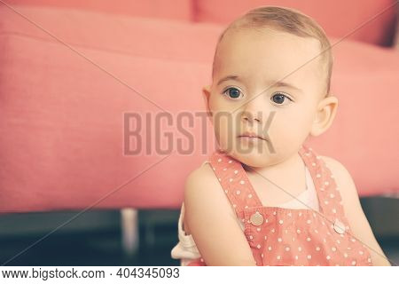 Pensive Baby Sitting On Floor In Living Room And Thinking About Something. Serious Little Girl In Re