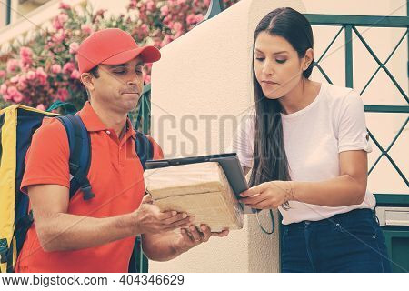 Postman Holding Clipboard With Order Data And Woman Signing It. Caucasian Courier With Backpack Wear