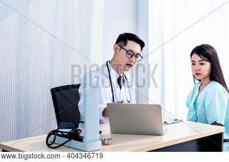 Asian Man Doctor Is Using Computer To Explain The Symptoms And Treatment Procedures Let The Woman Pa