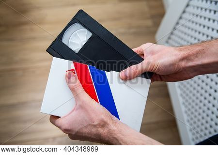 Male Hand Taking A Videotape, Video Cassette, Vhs Tape Out Of A Case, A Paper Cover.
