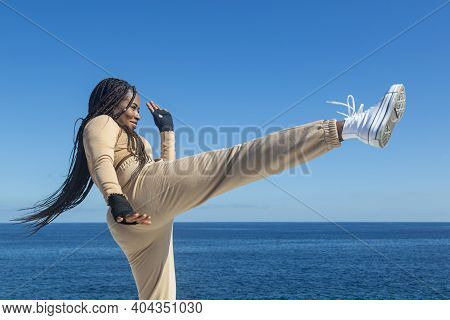 Portrait Of Young Beautiful Black Afro Girl Training, Throwing A Kick, Blue Sky And Sea Background,