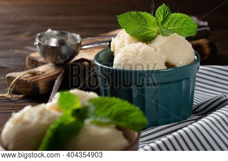 Vanilla Icecream Balls In Clay Bowls On Wooden Kitchen Table With Ice Cream Scoop Aside