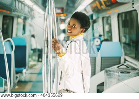 A Smiling Young African Woman Holds On To A Handrail While Standing On A Subway Train During Her Dai