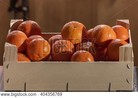 Tangerines (oranges, Clementines, Citrus) In A Wooden Box With A Rustic Background. Front View With