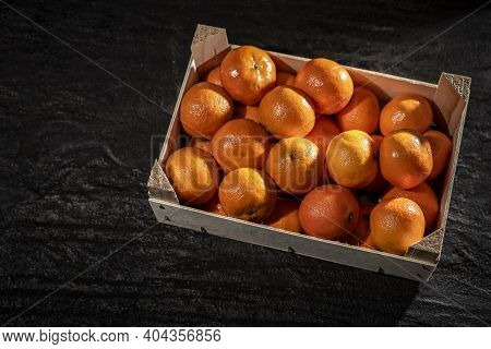 Tangerines (oranges, Clementines, Citrus) In Wooden Box On Garnet Tiles Background. Top View.tangeri