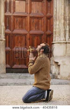 Man or monk praying in front of the church holding a cross