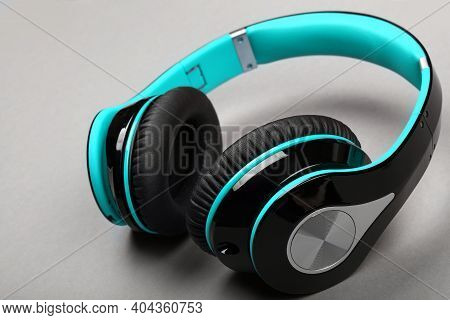 Close Up Modern Wireless Plastic Teal Blue Headphones With Big Cushions On Gray Table, High Angle Vi
