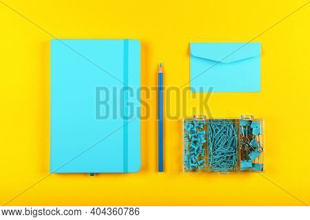 Neatly Organized Stationery Flat Lay Of Pastel Blue Notebook, Envelope, Pencil, Office Clips, Binder