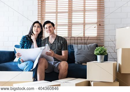 Asian Couple, Husband And Attractive Wife Looking And Discuss About Renovating The Old House To Be N