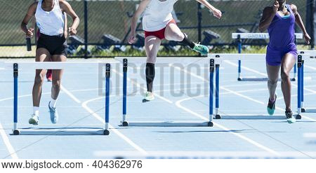 Three High School Girls Competing In A Four Hundred Meter Hurdle Race On An Outdaoor Track In The Su
