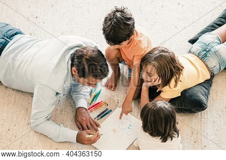 Concentrated Dad And Kids Lying On Carpet And Painting Doodles. Middle-aged Father Drawing With Colo