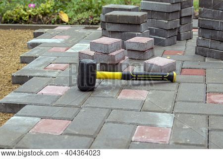 Laying Paving Stones On A Garden Path. Laying Gray Concrete Paving Slabs In The Yard On A Flat Sandy