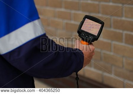 A Man Makes A Thermal Imager Check With A Camera, Looking For Heat Leaks From The House. Correct Con