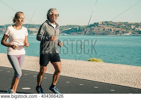 Active Retired Jogging Along River Bank Past Fishing Tackles. Water And Blue Sky In Background. Reti