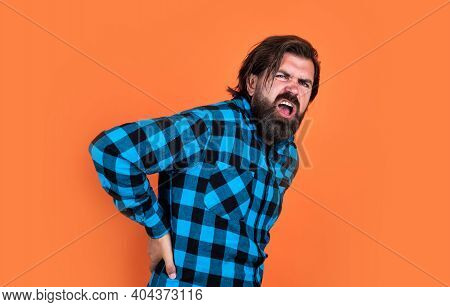 Radiculitis. Healthcare Concept. Brutal Handsome Man With Moustache. Mature Barber On Orange Backgro