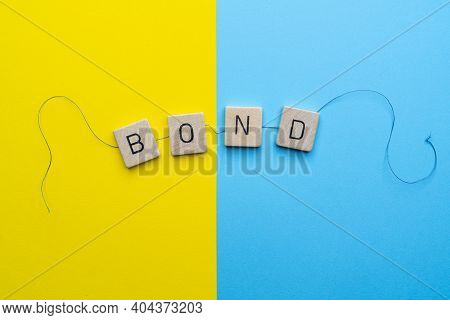 The Word Bond Formed With The Letters Linked Together By A Thread