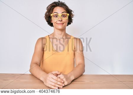 Young hispanic woman wearing casual clothes and glasses sitting on the table puffing cheeks with funny face. mouth inflated with air, crazy expression.