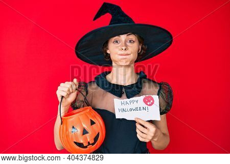 Young hispanic woman wearing witch costume holding pumpkin and happy halloween message puffing cheeks with funny face. mouth inflated with air, catching air.