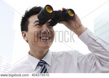 Businessman Looking Through A Hand-held Telescope, Smiling High Quality Photo