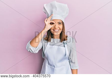 Young beautiful woman wearing professional cook uniform and hat doing ok gesture with hand smiling, eye looking through fingers with happy face.