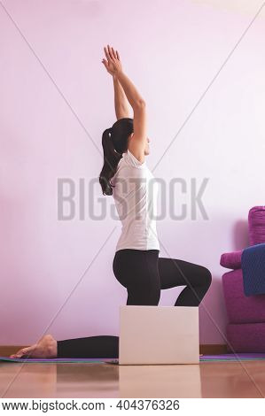 Young Happy Caucasian Woman, Practicing Yoga In The Living Room While Looking At Her Laptop. Health
