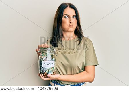Middle age brunette woman holding charity jar with money puffing cheeks with funny face. mouth inflated with air, catching air.