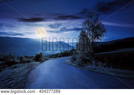 Countryside Road In Mountains At Night. Beautiful View In To The Distant Foggy Valley From The Top O