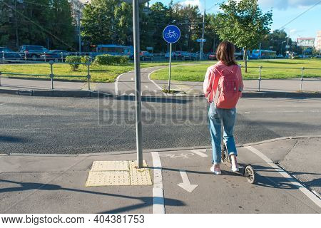 Girl On Scooter Summer In City. Stands With His Back, Crossroads, Waiting For Car To Pass. Free Spac