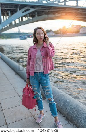 A Woman In Summer In City Stands By River Bank, Making A Phone Call, Dating And Meeting On Street, T