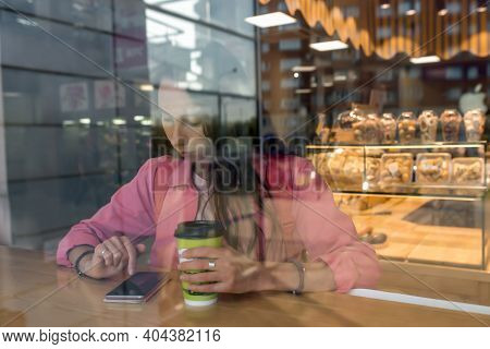 Woman In A City Cafe In Summer Reads Social Networks In Internet Application. Background Of Coffee T