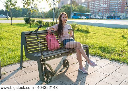 Woman In Summer In A City Park, Resting After Work, In Hand A Coffee Tea Cup. Rest And Lunch After W