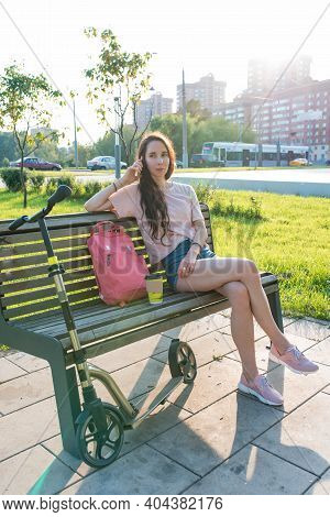 Woman In A City Park In Summer Calls On Phone, Rests After Work, A Cup Of Coffee Tea. Rest And Lunch