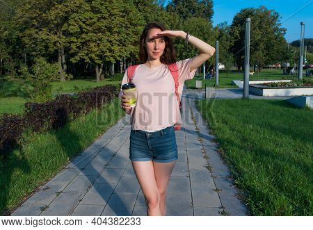 Woman In Summer In A City Park Looks Into Distance, Covers Herself With Her Hand From Sun, A Meeting