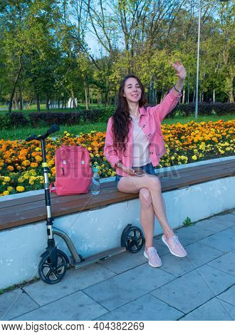 Woman In Summer In A City Park Waves Her Hand, Happy Smiles Rejoices, Meeting And A Date, Scooter Sh